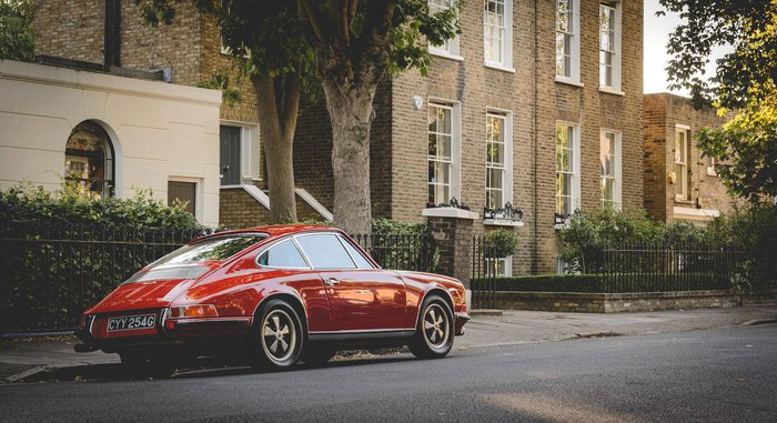 Classic red porsche parked on street